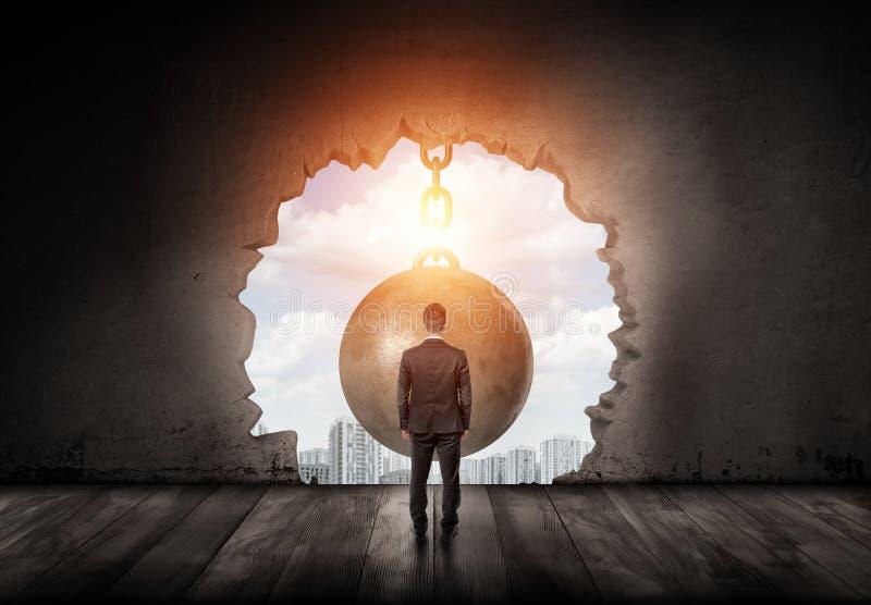 站立与被转动和调查城市的商人通过一个巨型击毁的球做的墙壁孔 库存照片