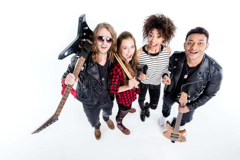 站立与话筒的年轻摇滚乐队大角度看法  免版税库存图片