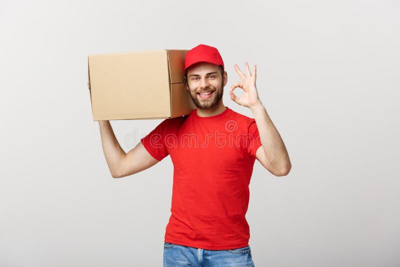 站立与邮包箱子的红色盖帽的快乐的年轻送货人被隔绝在显示好姿态的白色背景 库存图片
