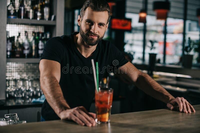 站立与酒精饮料的英俊的男服务员 免版税库存图片