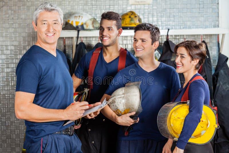 站立与队的愉快的消防员 库存图片
