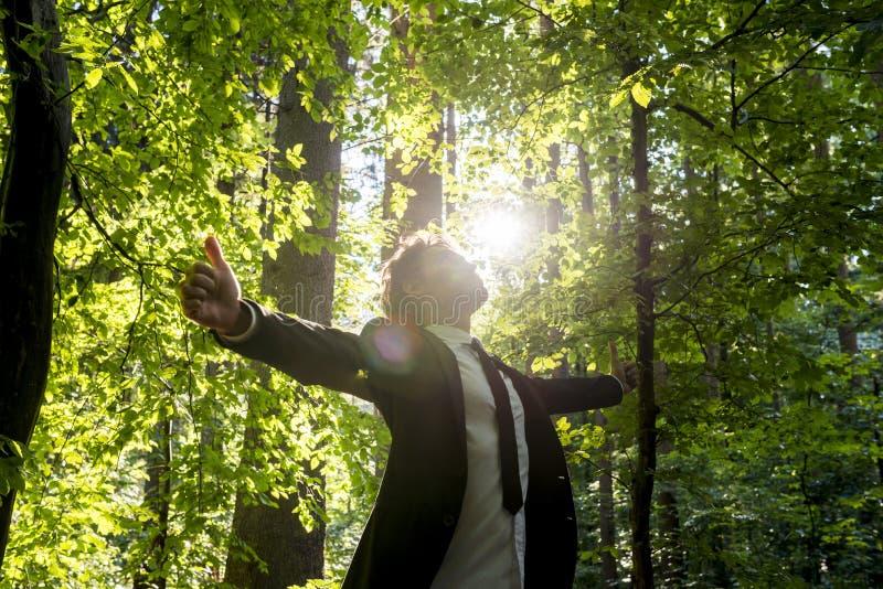 站立与他的商人在森林地武装扩张 免版税库存照片