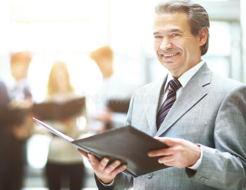 站立与他的职员的商人在背景中在办公室 免版税库存图片