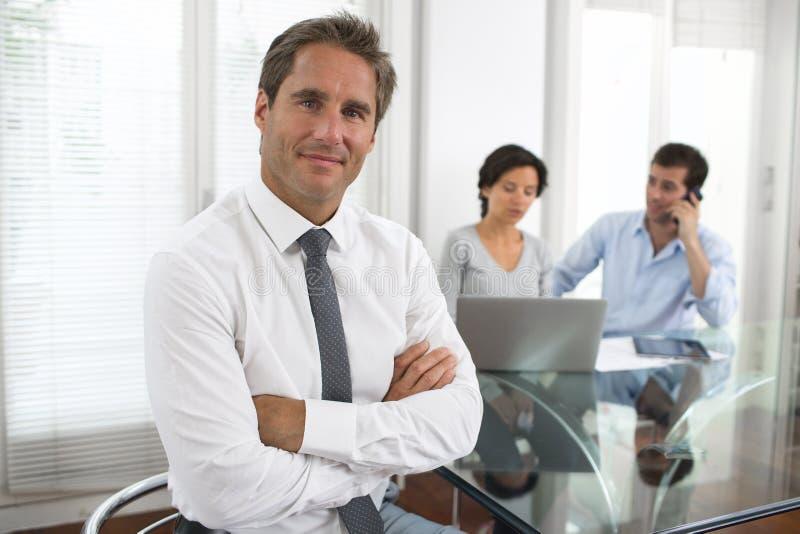 站立与他的职员的成功的商人在背景中在 免版税库存图片