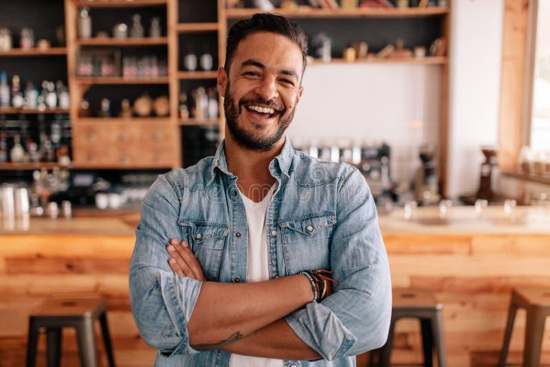 站立与他的胳膊的愉快的年轻人在咖啡馆横渡了 免版税库存照片