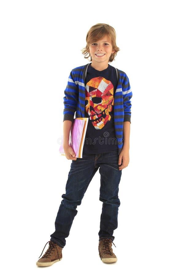 站立与他的练习簿的少年男小学生 免版税图库摄影