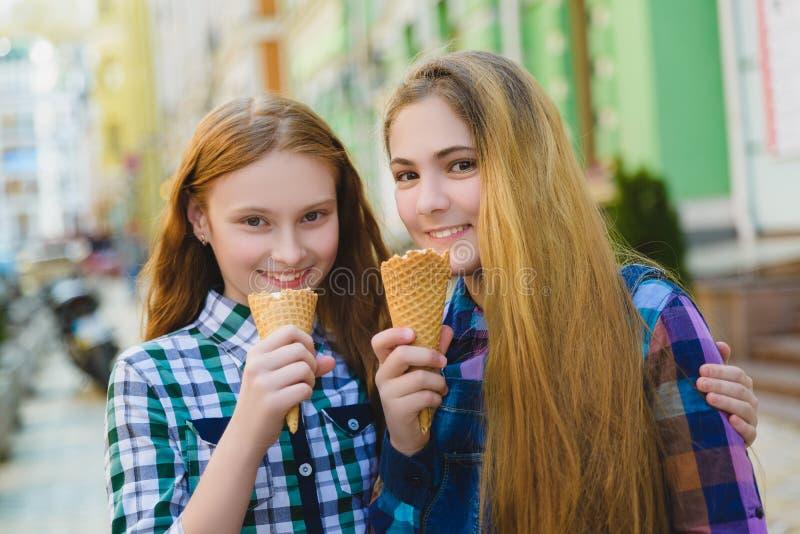 站立两个少年的女孩画象一起吃冰淇凌 库存图片