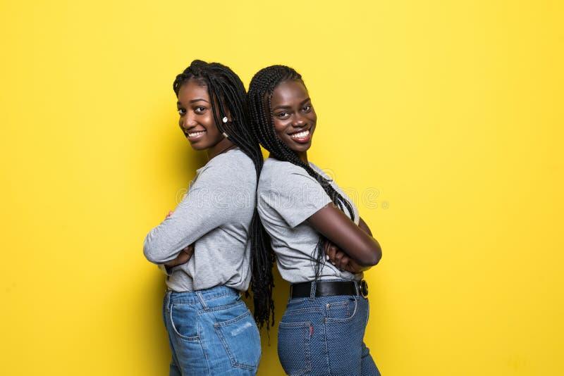 站立两名微笑的年轻非洲的妇女画象一起隔绝在黄色背景 库存照片