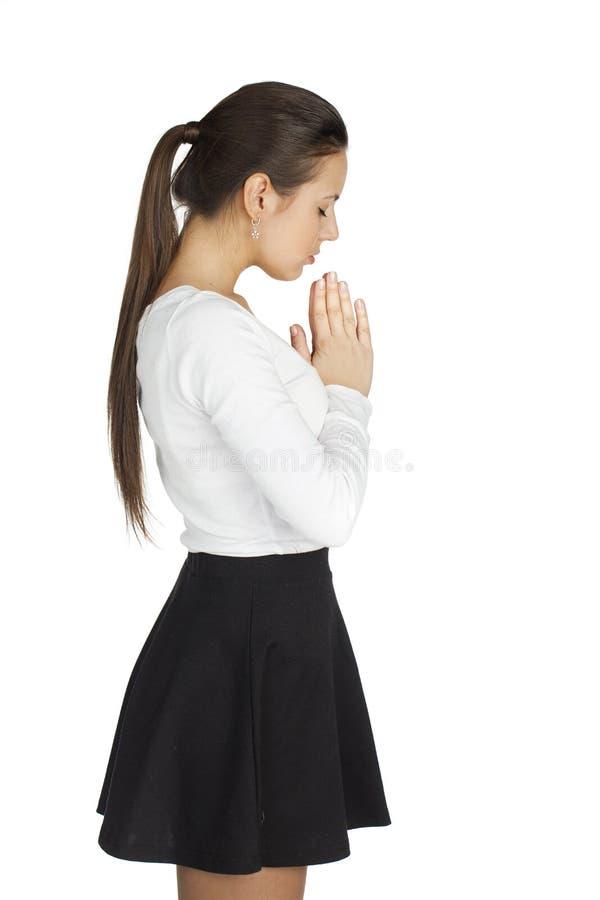 站立为白色背景的深色的妇女用她的手折叠 免版税库存照片