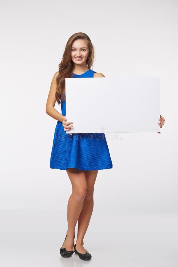 站立全长美丽的妇女后边,举行白色bl 免版税库存照片