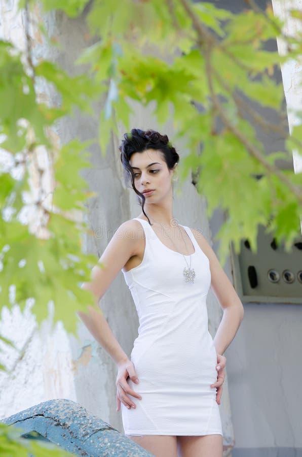 站立前面老房子的俏丽的夫人穿一件紧的短的白色礼服 免版税库存照片