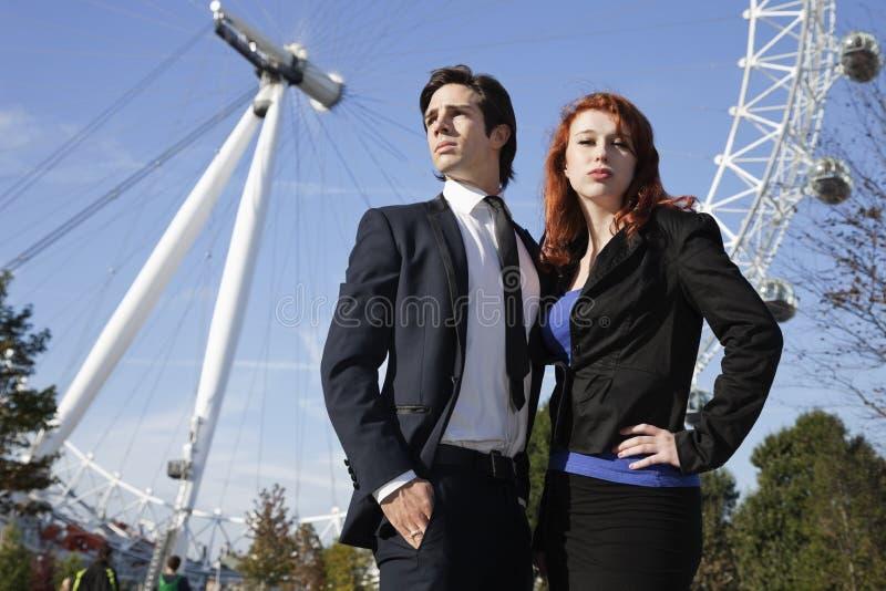 站立反对与同事,伦敦,英国的伦敦眼的确信的年轻女实业家画象  免版税库存图片