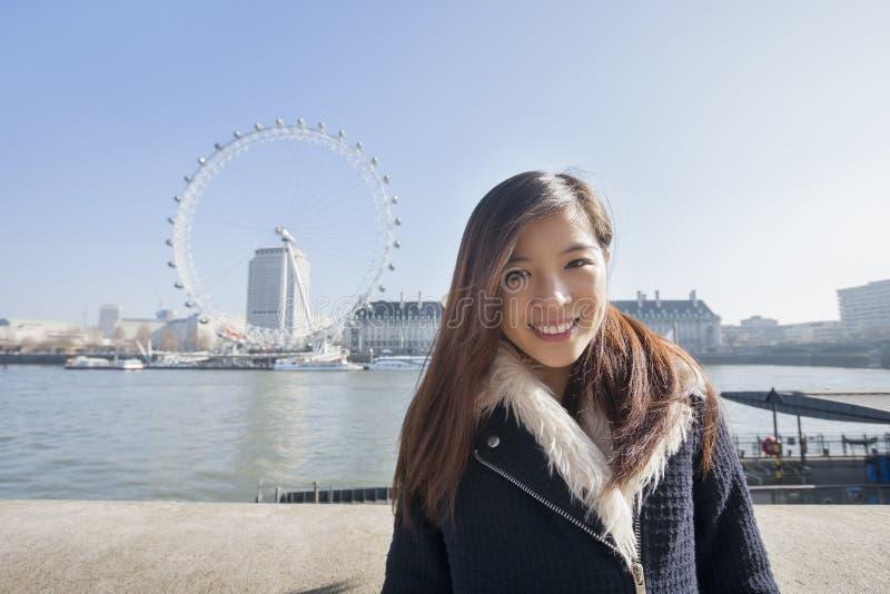 站立反对伦敦眼的愉快的少妇画象在伦敦,英国,英国 免版税库存图片