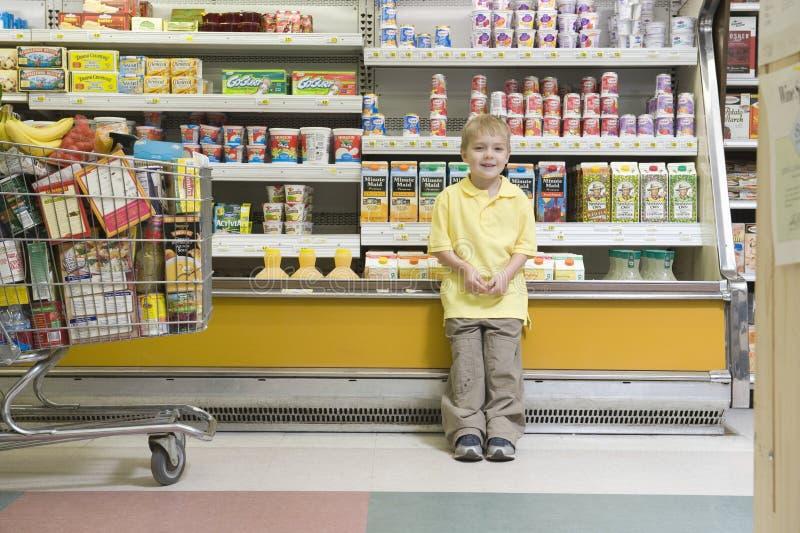 站立反对冰箱柜台的男孩在超级市场 库存照片