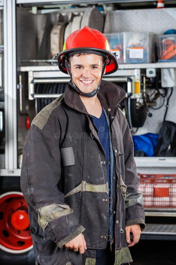 站立反对卡车的愉快的消防员 免版税图库摄影