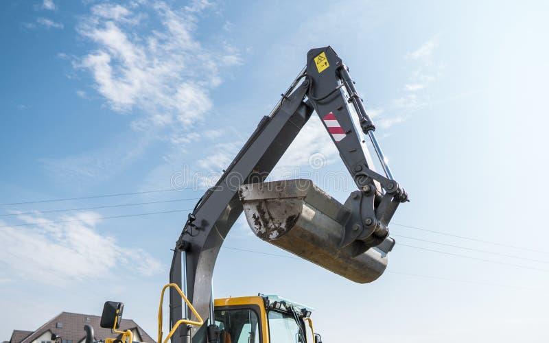 站立反对晴朗的多云天空在修路时和修理沥青的桶黄色挖掘机装载者 免版税库存照片