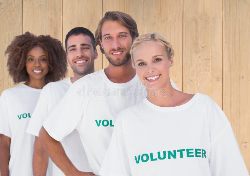 站立反对木背景的小组志愿者 库存照片