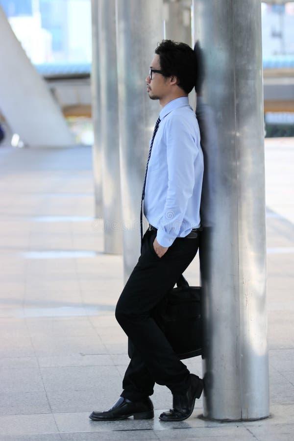站立反对杆的确信的年轻亚裔商人画象在都市城市背景 库存图片