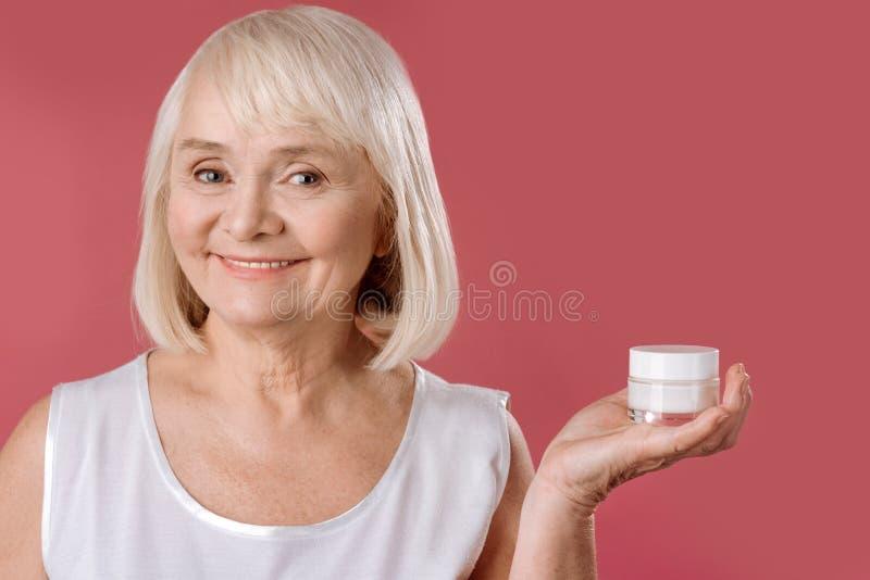 站立反对桃红色背景的高兴年长妇女 免版税库存照片