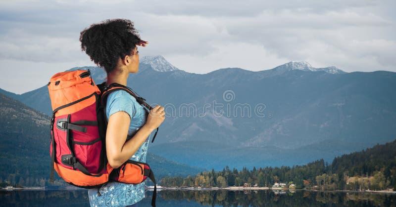站立反对湖和山的远足者侧视图 免版税库存图片