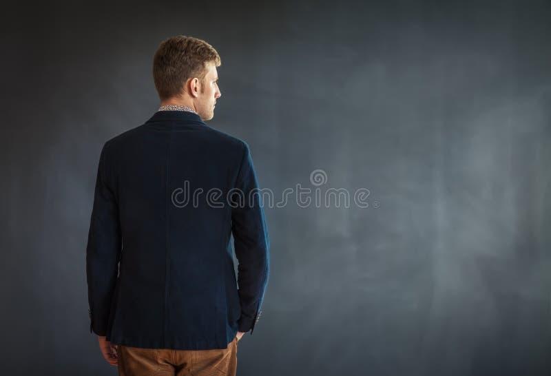 站立反对灰色墙壁背景的年轻人背面图 库存图片