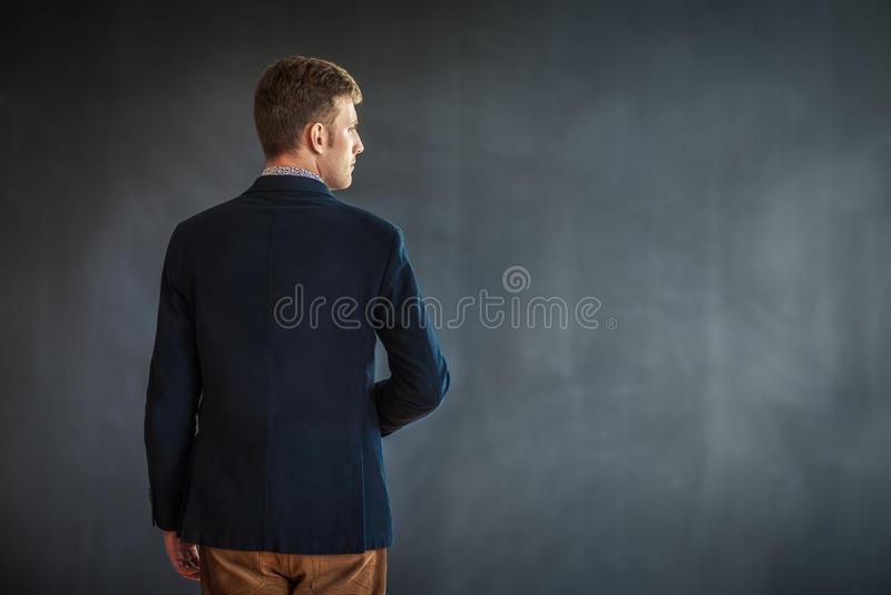 站立反对灰色墙壁背景的年轻人背面图 库存照片