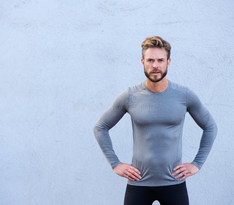 站立反对灰色背景的严肃的健身教练员 免版税图库摄影