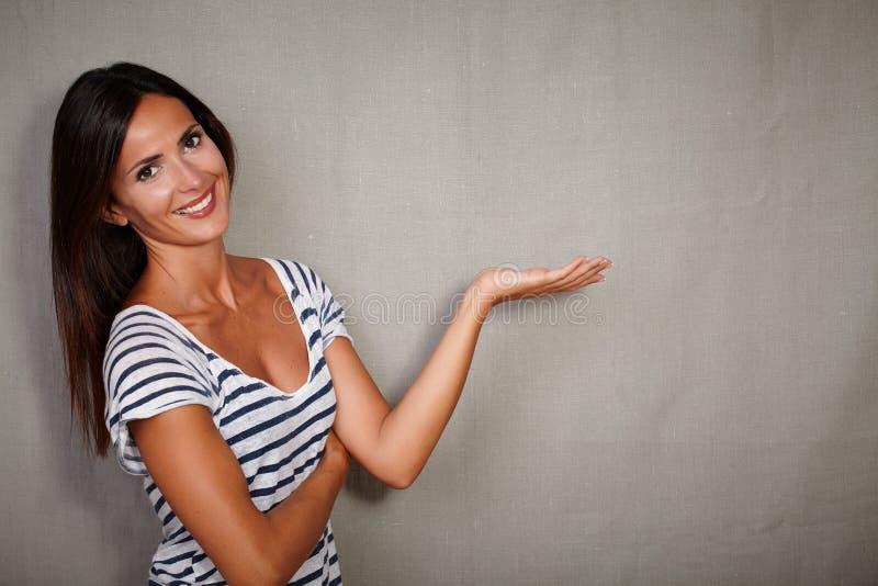 站立反对灰色背景的悦目女孩 免版税图库摄影