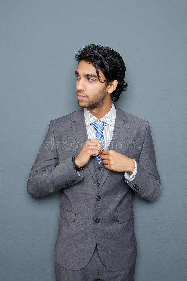 站立反对灰色背景的英俊的年轻商人 免版税库存照片