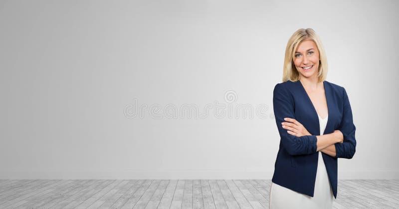 站立反对白色墙壁背景的愉快的女商人 免版税库存照片