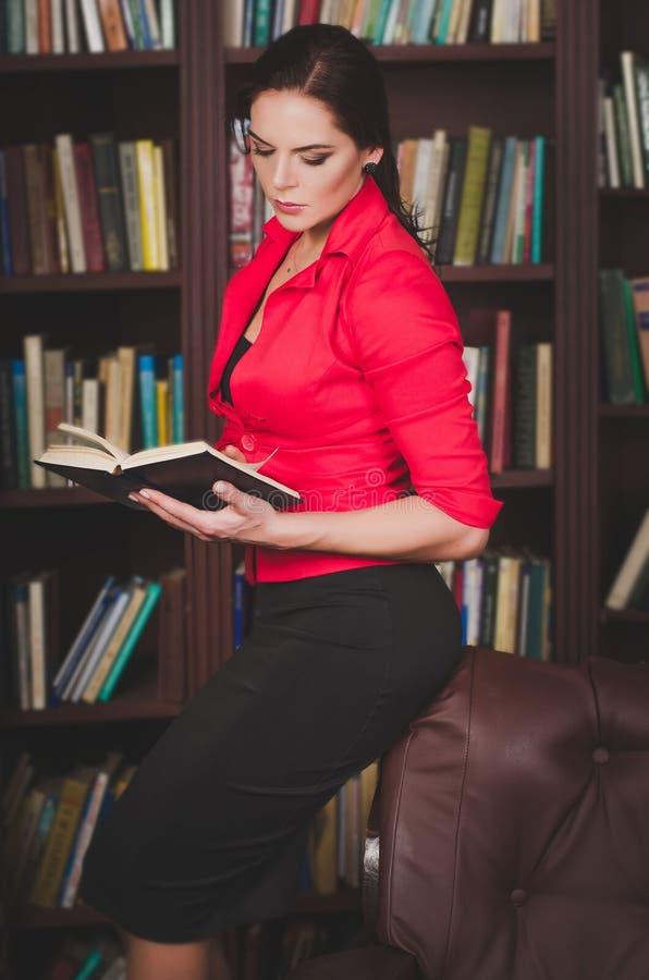 站立反对的办公室服装的可爱的女商人 库存照片