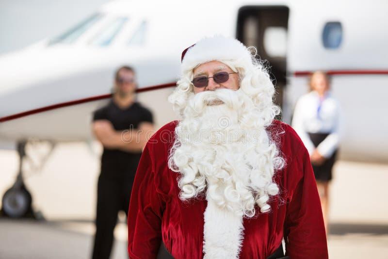站立反对私人喷气式飞机的圣诞老人服装的人 库存照片