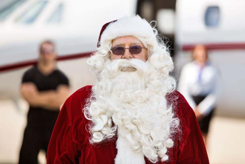 站立反对私人喷气式飞机的圣诞老人 库存图片
