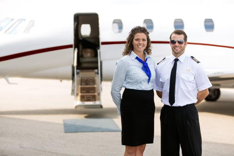 站立反对私人喷气式飞机的空中小姐和飞行员 免版税库存照片