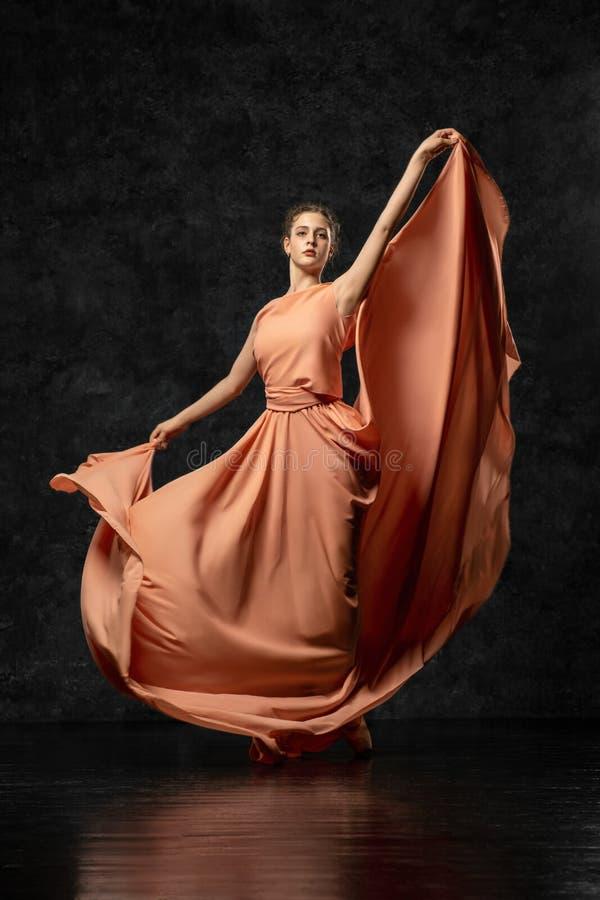 站立反对背景黑墙壁的一位年轻优美的舞蹈家穿戴在一件长的桃子滚滚向前的礼服 图库摄影