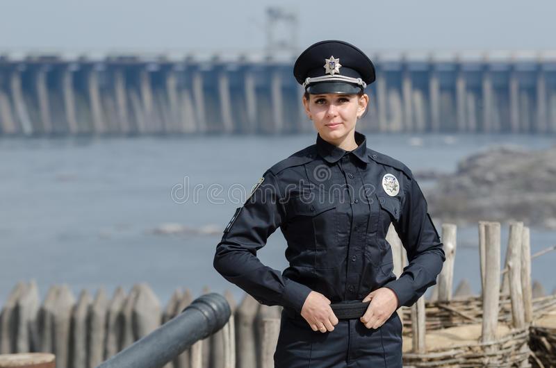 站立反对都市背景的快乐的女性乌克兰警察 免版税库存图片