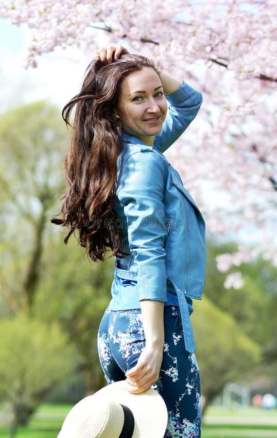 站立可爱的美丽的白种人的妇女摆在开花的日本樱桃背景  免版税库存图片