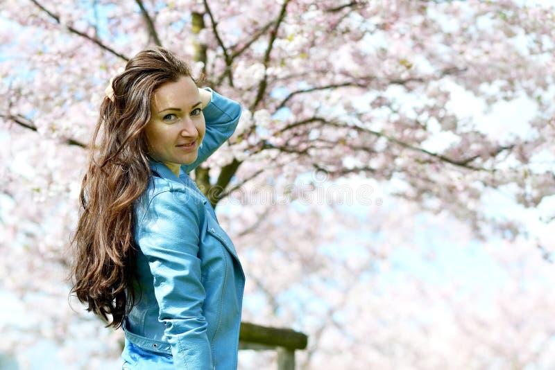 站立可爱的美丽的白种人的妇女摆在开花的日本樱桃背景  图库摄影