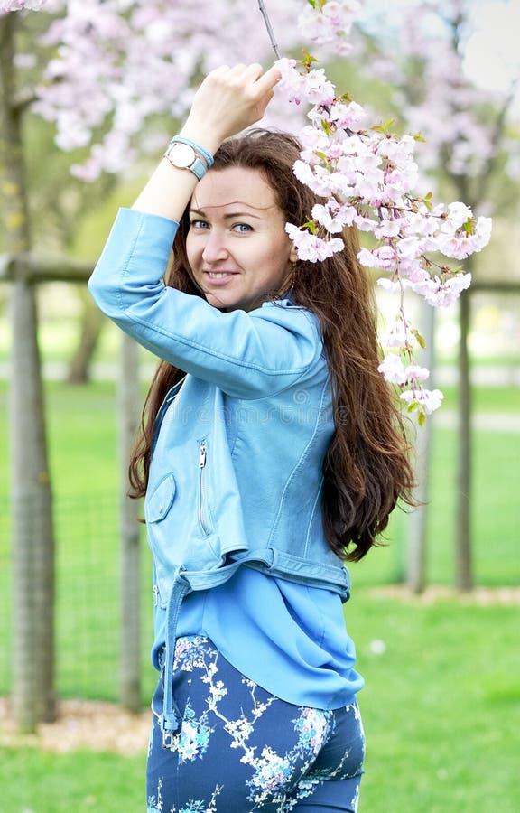 站立可爱的美丽的白种人的妇女摆在开花的日本樱桃背景  免版税库存照片