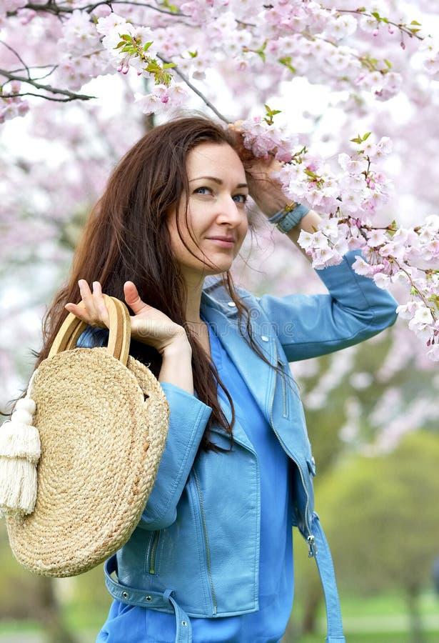 站立可爱的美丽的白种人的妇女摆在开花的日本樱桃背景  库存照片