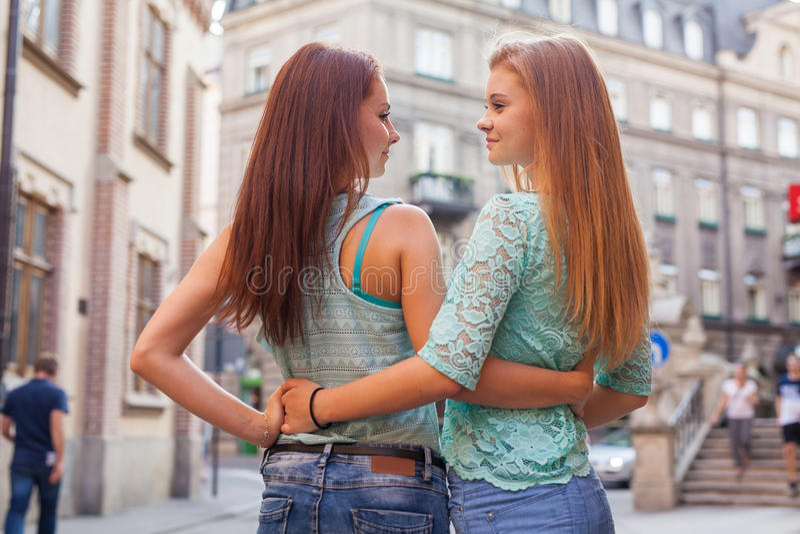 站立后话和拥抱的女孩画象  都市ba 库存照片