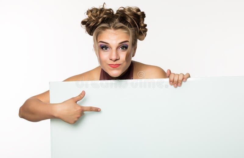 站立后面和倾斜在一张白色空白的广告牌或招贴,您的文本的拷贝空间的妇女 库存照片
