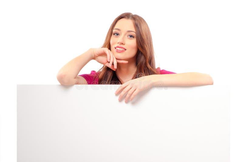 站立后面和倾斜在白色空白的妇女 免版税图库摄影