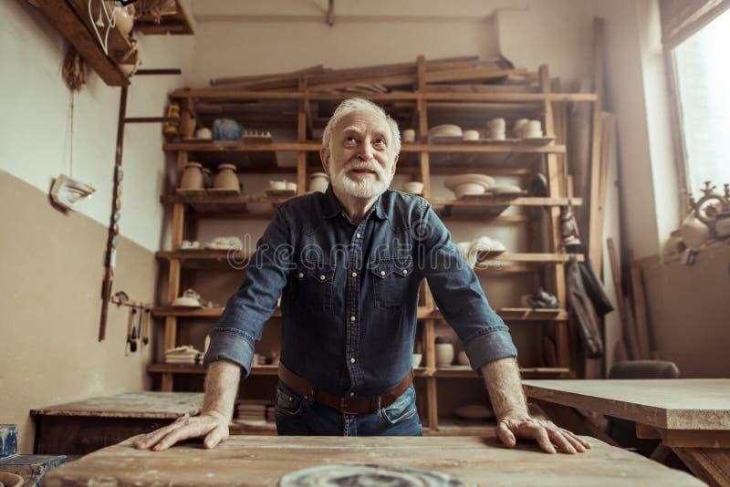 站立和倾斜在桌上的资深陶瓷工反对与瓦器物品的架子在车间 免版税图库摄影