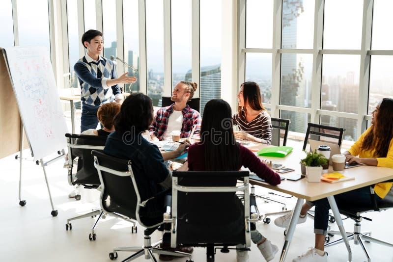 站立和做介绍在现代办公室愉快谈话和群策群力与队的年轻亚洲创造性的商人 Casu 免版税库存图片