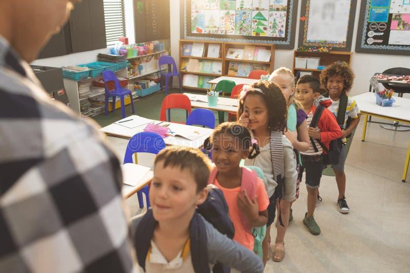 站立和形成一个队列的学校孩子在教室在学校 图库摄影