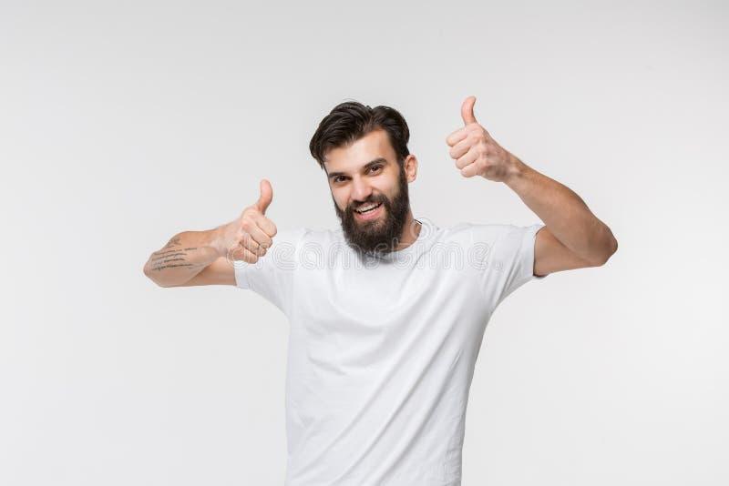 站立和微笑反对白色背景的愉快的商人 免版税库存照片