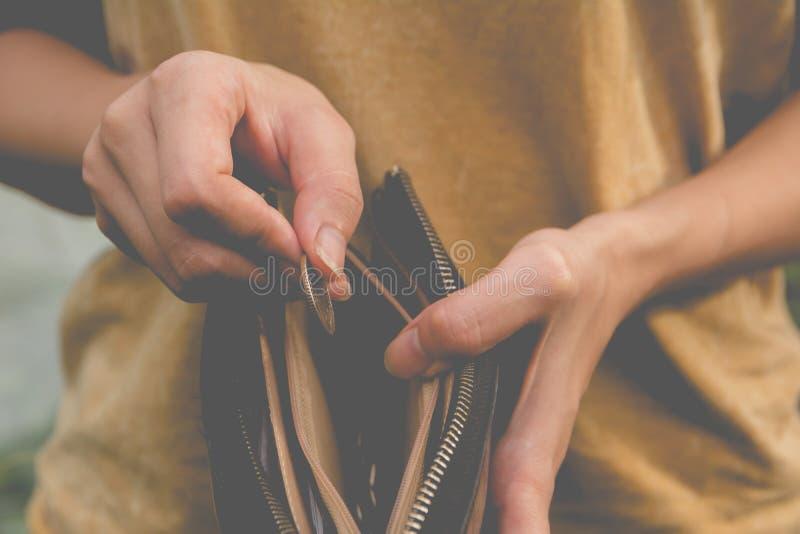 站立和拿着与钱包的特写镜头妇女金钱硬币空 库存照片