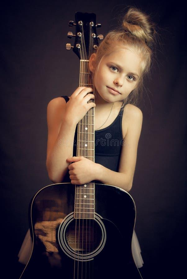 站立和拿着吉他的美丽的女孩 免版税库存照片
