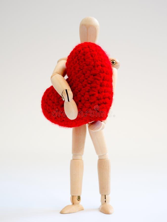 站立和拿着在白色屏幕背景的木木偶红色心脏 拿着与爱和关心的木木偶心脏 免版税库存图片